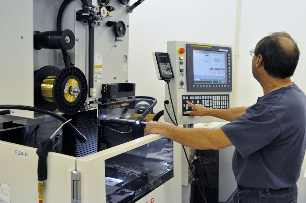 man working on Wire EDM or an Electrical Discharge Machine