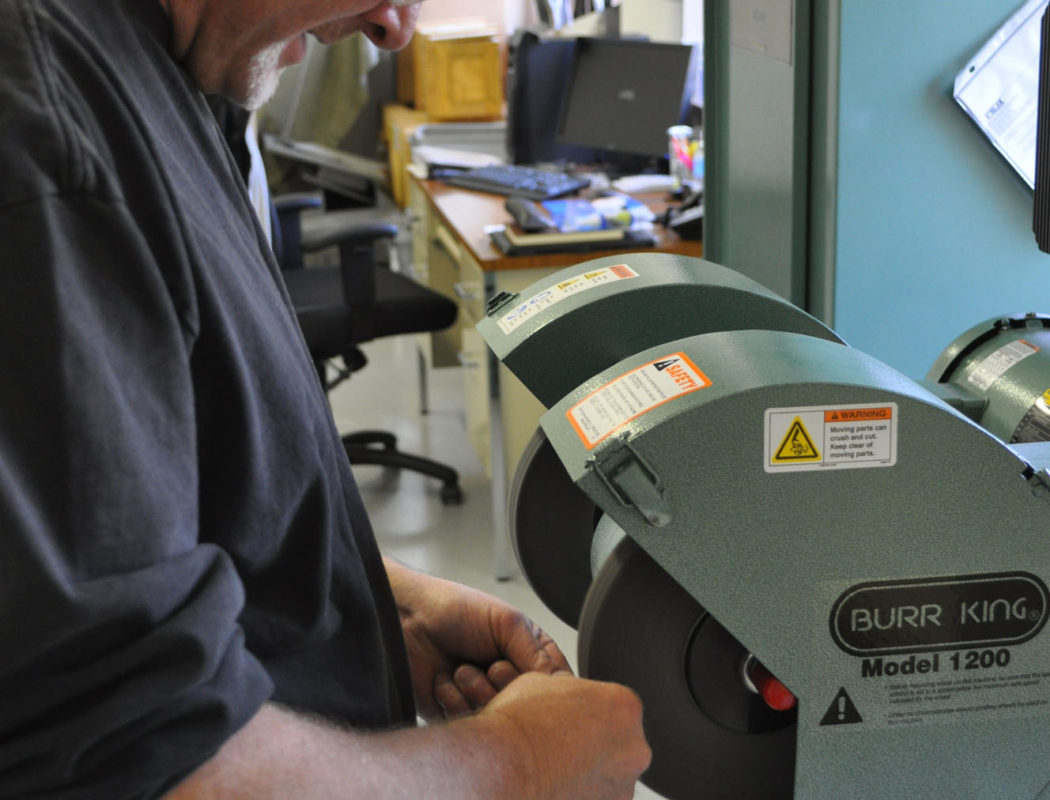 man working with a BURR KING Model 1200 Deburring & Polishing Machine