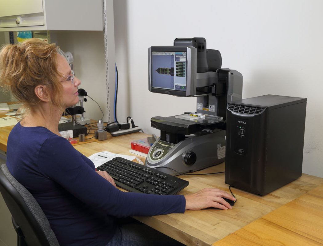 woman working with a Keyence IM-6225 Image Dimension Measuring System